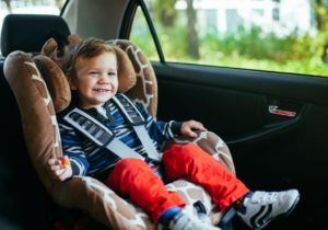 Happy kid sitting in his carseat.